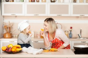 Little cute girl with her mother eating orange while cooking. Kitchen interior. Concept for young kitchen hands