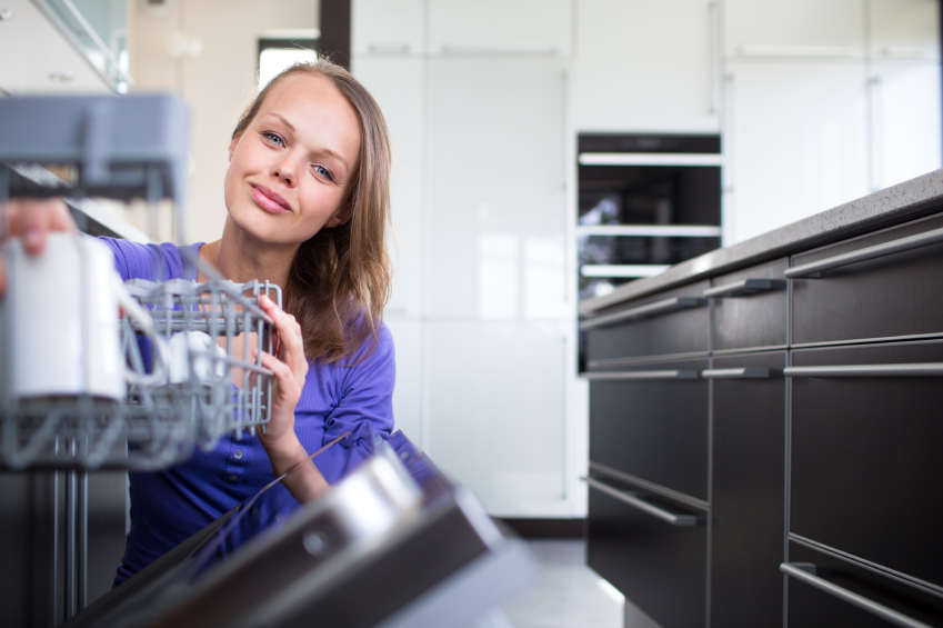 Pretty, young woman in her modern and well equiped kitchen putting cups into the dishwasher - an appliance that helps her keep the home tidy