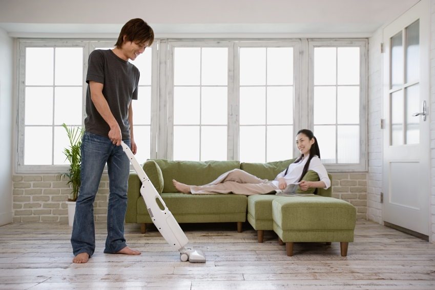 Man vacuuming and woman on sofa