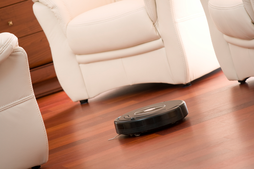 Home vacuum cleaning robot in action on genuine wooden floor. Selective focus on robot.