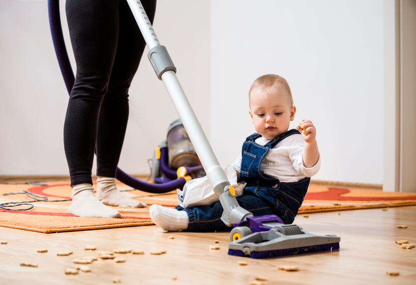 Woman cleaning with vacuum cleaner, baby sitting on floor and biscuits all around